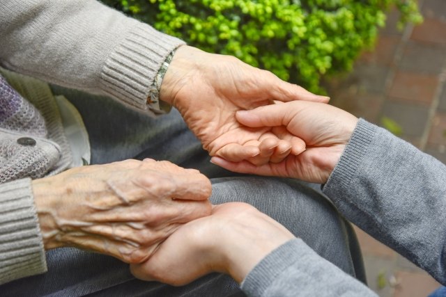 高齢者の手を取る光景