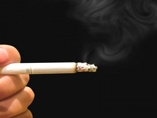 火のついたタバコを持っている手