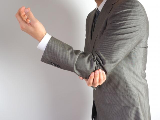 肘を抑えるスーツ姿の男性